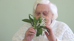 Old Woman Smelling Flowers Lily Of The Valley stock footage