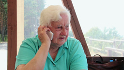 Elderly woman is talking on the phone ビデオ