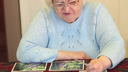 Elderly woman is watching own pictures Live Action
