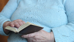The hands of an old woman holding prayer book Live Action