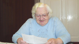 Senior woman reading funny news in the letter Live Action