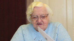 Senior woman reading letter. 2 Footage