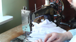 Old woman sews on the old sewing machine 3 Live Action