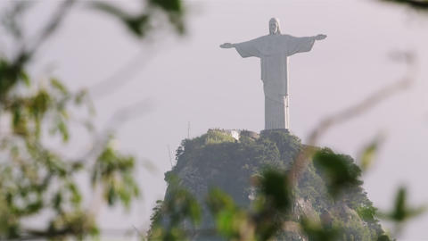 Christ statue atop Corcovado seen through tree foliage Footage