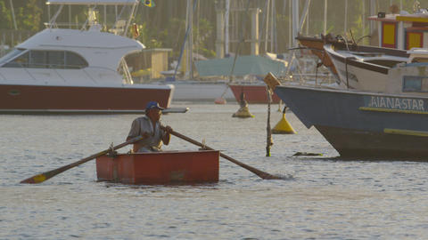 Slow motion of a man rowing a boat amidst a variety of larger craft Footage