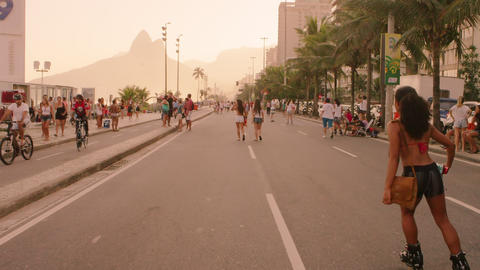 Slow motion tracking shot of Brazilian girl rollerblading down Avenida Vieira So Footage