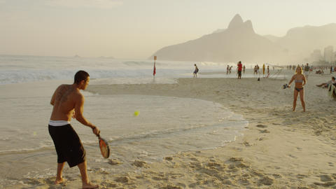 Slow motion shot of a couple playing tennis on Ipanema beach Footage