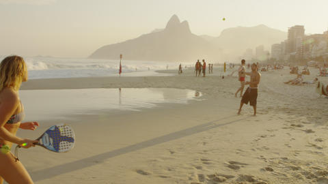 Slow motion shot of a couple playing tennis on Ipanema beach at dusk Footage