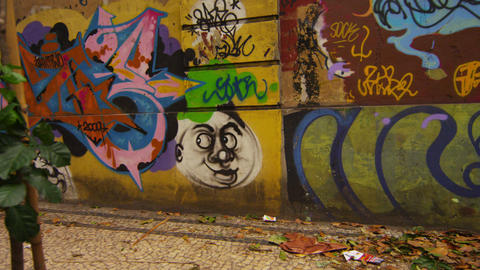 Tracking down dimmly lit street showing wall covered in tags Footage