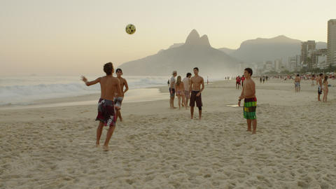 RIO DE JANEIRO-JUNE16: Boys kicking a football at the beach on June 16, 2013 in  Footage