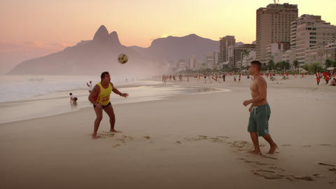 Two Men Playing Football On Ipanema Beach stock footage