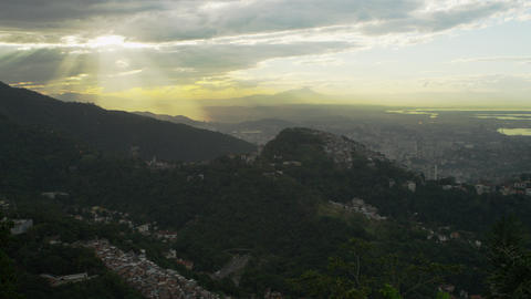 Static shot of the sun coming through the clouds over Rio de Janeiro's hills Footage