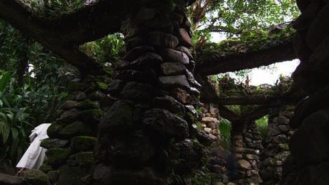 Nuns walking near stone structure columns in Jardim Botanicos Footage