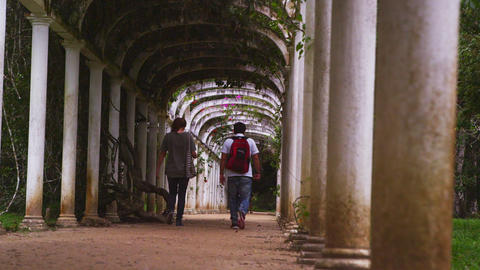 Panning shot of male and female walking under arches Footage