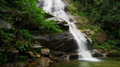 Slow motion shot of a jungle waterfall cascading down a rocky outcropping into a Footage
