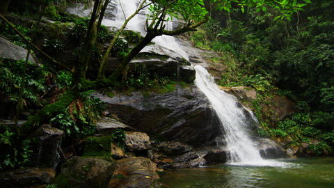 Tracking shot of a jungle waterfall cascading into a deep green pool Footage