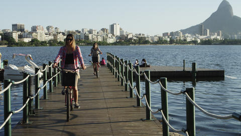 Women biking off small lake pier Footage