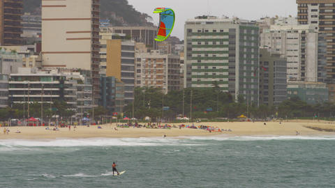 Pan shot of parasailing surfer with Cityscaper in the background Footage