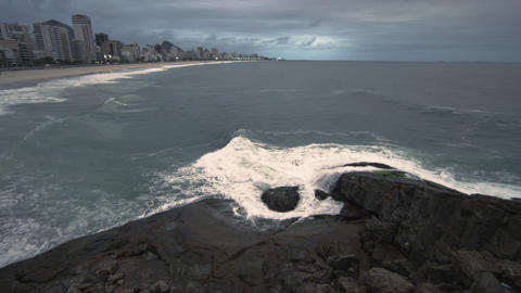 Slow pan of Rio skyline along the beach at dusk in Rio de Janeiro, Brazil Footage