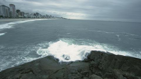 Slow pan of waves splashing on rocks along the coast in Rio de Janeiro, Brazil Footage