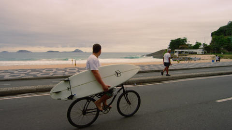 RIO DE JANEIRO-JUNE 23: Man bikes while holding surfboard near Ipanema Beach on  Footage