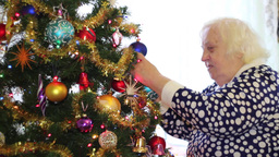 Elderly woman decorates christmas tree and smiles Footage