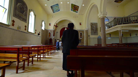 woman sits in a church and prays in Santiago Footage