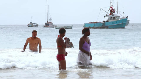 two women and a man bathe at the beach in Tarrafal Footage
