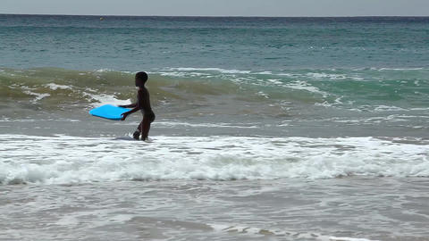 boy surfs with a blue boogie board at Tarrafal Footage