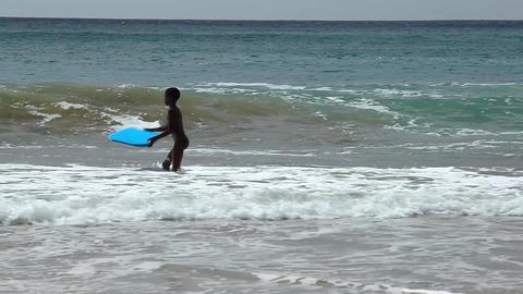 boy surfs with a blue boogie board at Tarrafal Footage