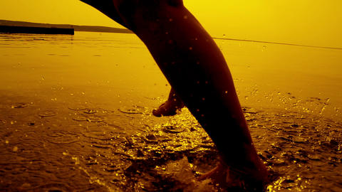 SLOW MOTION: Girl running in shallow water at suns Footage