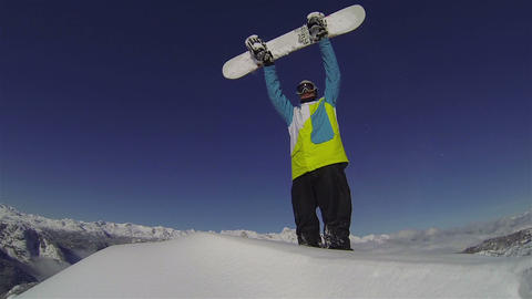 Snowboarder reaches the top of the mountain Footage