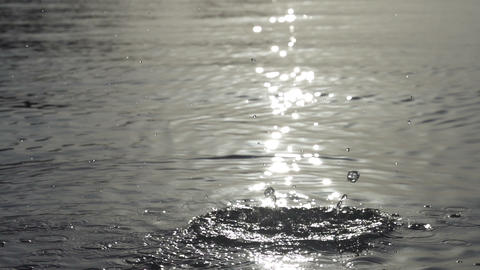 SLOW MOTION: Stone thrown into the water, sun refl Footage