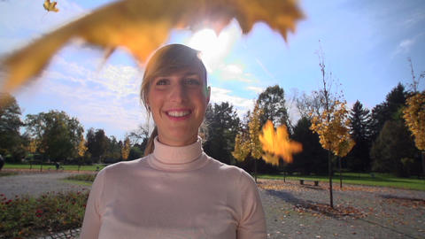 SLOW MOTION: Young female throwing leaves Footage