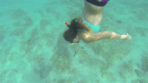 UNDERWATER SLOW MOTION: Young woman snorkeling Footage