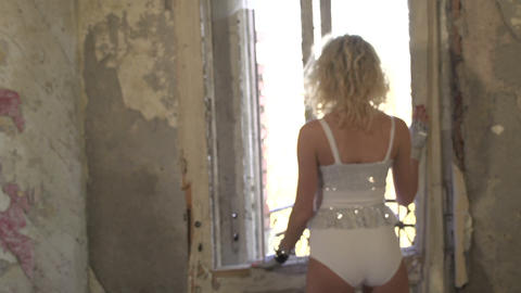 Woman looking through the window of a ruined house Footage