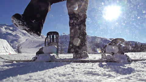 SLOW MOTION: Snowboarder strapping in Live Action