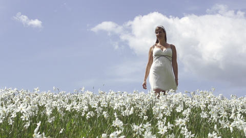 SLOW MOTION: Young woman walking in flower field Live Action