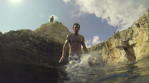 SLOW MOTION: Young man jumps into the ocean Footage