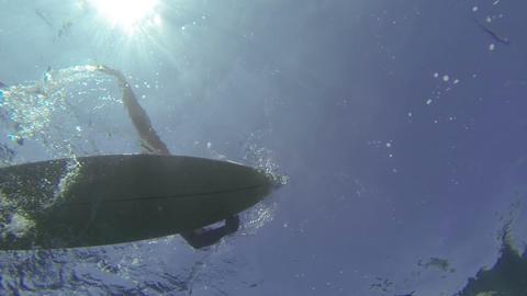 UNDERWATER: Surfer paddling in clear water Footage