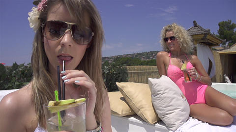 SLOW MOTION: Young women sipping cocktails poolsid Footage