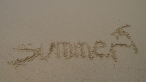 Word summer written in the sand and washed away Footage