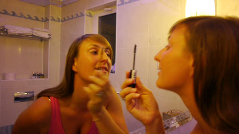 Young woman applying makeup in the mirror Footage