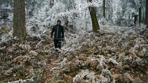 AERIAL: Young man walking in the frozen forest Footage