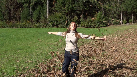 SLOW MOTION: Autumn leaves falling on young woman Footage