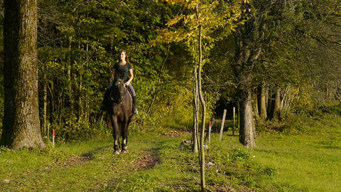 Young woman riding through the woods Footage