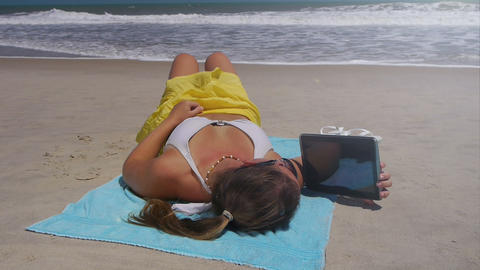 Young woman reading digital tablet on vacations Footage