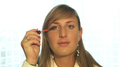 Young woman putting on makeup, looking directly at Footage