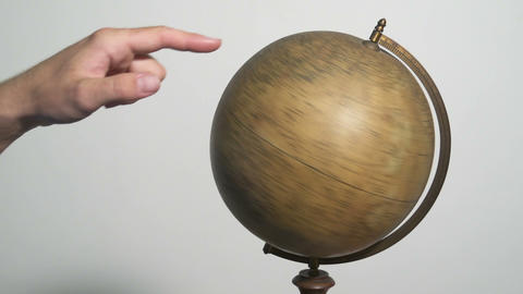Man spinning a globe and pointing on it Footage
