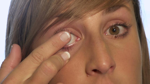 Young woman holding contact lense on a finger and  Footage